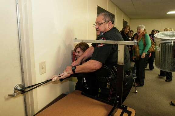 Tammy Harlan, of Humble ISD, and Klein ISD Police Chief Guadalupe Rocha secure a door with an ethernet cord as participants of the Intruderology training make a barricade during a hostile intruder simulation in the HISD Police Department headquarters.