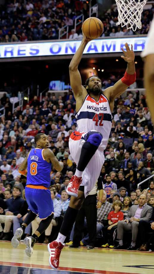 Washington Wizards center Nene (42), of Brazil, dunks as New York Knicks guard J.R. Smith (8) watches in the second half of an NBA basketball game, Wednesday, Feb. 6, 2013, in Washington. The Wizards won 106-96. (AP Photo/Alex Brandon) Photo: Alex Brandon
