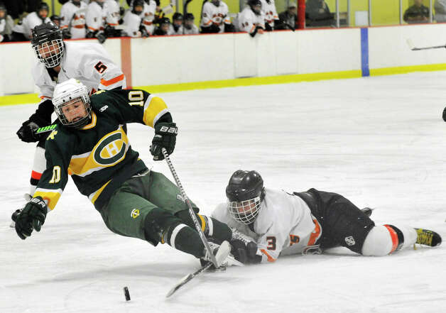 Trinity Catholic's Griffin Northrop is tripped up by Stamford's Bill Santora during the city championship game at Terry Conners Rink in Stamford on Wednesday, Feb. 6, 2013. Trinity Catholic beat Stamford, 2-1. Photo: Jason Rearick / The News-Times