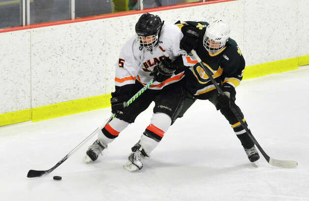 Stamford's Cole Savona keeps the puck from Trinity Catholic's Colin Bernard during the city championship game at Terry Conners Rink in Stamford on Wednesday, Feb. 6, 2013. Trinity Catholic beat Stamford, 2-1. Photo: Jason Rearick / The News-Times