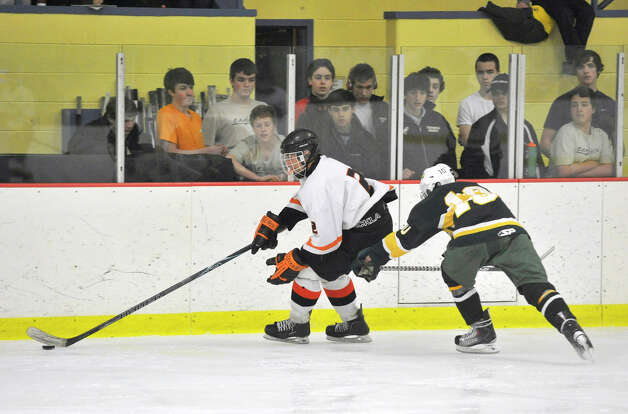 Stamford's Andrew Tuccinardi keeps the puck from Trinity Catholic's Griffin Northrop during the city championship game at Terry Conners Rink in Stamford on Wednesday, Feb. 6, 2013. Trinity Catholic beat Stamford, 2-1. Photo: Jason Rearick / The News-Times