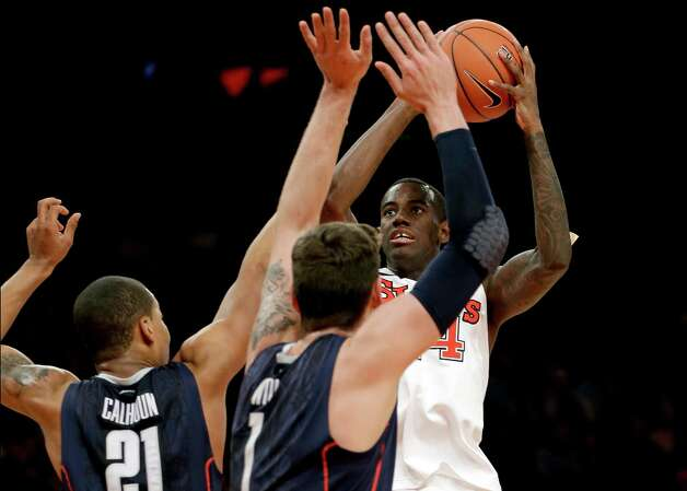 St. John's forward Jakarr Sampson (14) shoots over Connecticut guard Omar Calhoun (21) and center Enosch Wolf (1) in the second half of their NCAA college basketball game at Madison Square Garden in New York, Wednesday, Feb. 6, 2013.  St. John's won 71-65. (AP Photo/Kathy Willens) Photo: Kathy Willens, Associated Press / AP