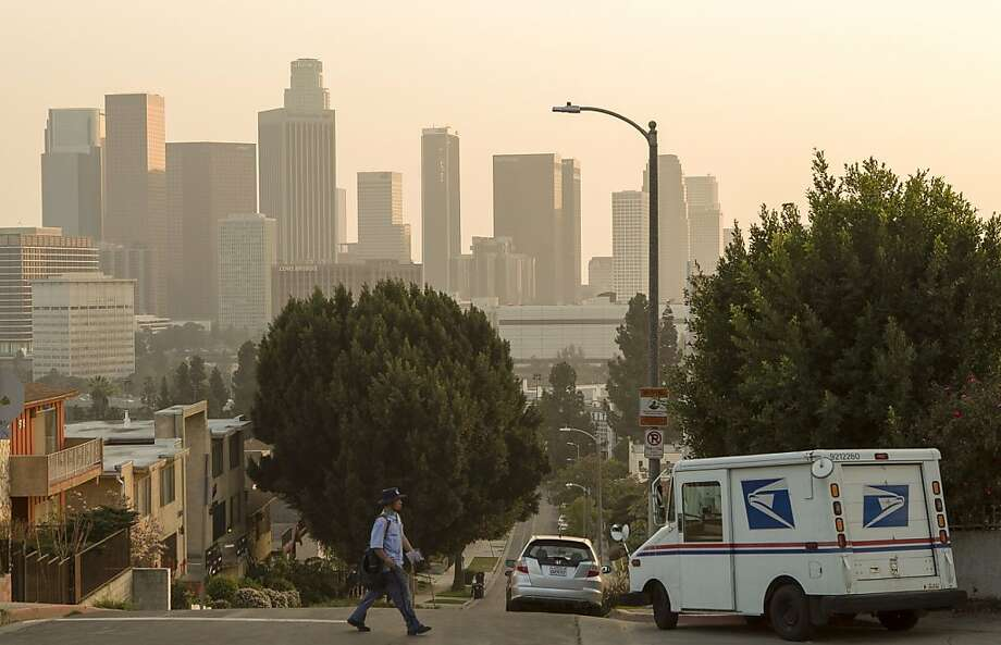 A 25-year veteran U.S. mail carrier who identified himself only as Keo walks his route in Los Angeles Wednesday, Feb. 6, 2013. The financially struggling U.S. Postal Service wants to stop delivering mail on Saturdays but continue to deliver packages six days a week under a plan aimed at saving about $2 billion a year.(AP Photo/Damian Dovarganes) Photo: Damian Dovarganes, Associated Press