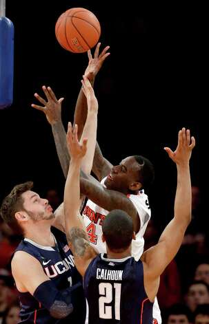 St. John's forward Jakarr Sampson (14) tries to tip the ball to a teammate as Connecticut center Enosch Wolf (1) and guard Omar Calhoun (21) defend in the first half of their NCAA college basketball game at Madison Square Garden in New York, Wednesday, Feb. 6, 2013. St. John's won 71-65. (AP Photo/Kathy Willens) Photo: Kathy Willens, Associated Press / AP