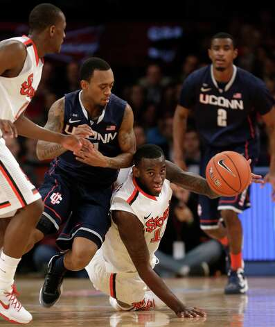 St. John's forward Jakarr Sampson (14) tries to pass a loose ball from the floor after Connecticut guard Ryan Boatright (11) lost the ball in the first half of their NCAA basketball game at Madison Square Garden in New York, Wednesday, Feb. 6, 2013.  (AP Photo/Kathy Willens) Photo: Kathy Willens, Associated Press / AP