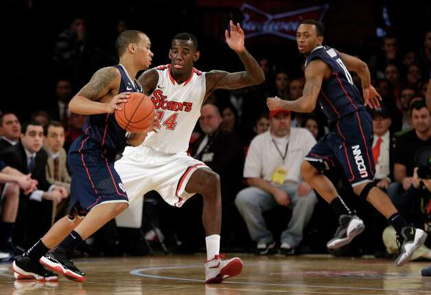St. John's forward Jakarr Sampson (14) defends as Connecticut guard Omar Calhoun (21) drives to the basket in the second half of their NCAA college basketball game at Madison Square Garden in New York, Wednesday, Feb. 6, 2013.  St. John's defeated Connecticut 71-65. (AP Photo/Kathy Willens) Photo: Kathy Willens, Associated Press / AP