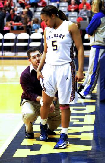 UAlbany's Ebone Henry (5) is helped by a trainer while playing against UMBC's during their America E