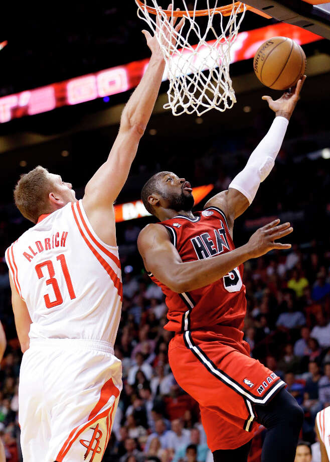Heat guard Dwyane Wade shoots against Rockets center Cole Aldrich. Photo: Wilfredo Lee, Associated Press / AP