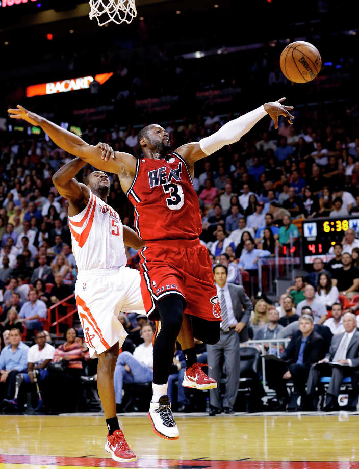 Heat guard Dwyane Wade (3) is stripped of the ball as he goes up for a shot against Rockets guard Toney Douglas. Photo: Wilfredo Lee, Associated Press / AP