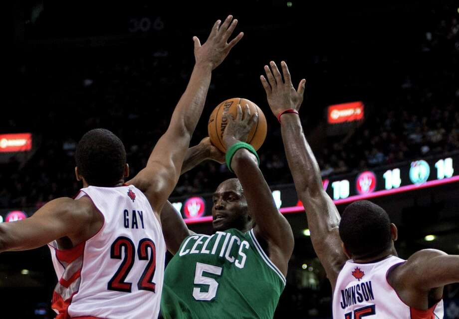 Boston Celtics forward Kevin Garnett (5) passes the ball under heavy pressure from Toronto Raptors forwards Rudy Gay (22) and Amir Johnson, right, during second-half NBA basketball game action in Toronto, Wednesday, Feb. 6, 2013. (AP Photo/The Canadian Press, Frank Gunn) Photo: Frank Gunn
