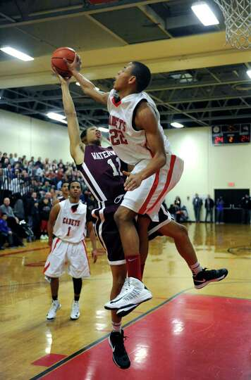 Albany Academy's Ray Jerome blocks a shot by Watervliet's Shane Ray during their boy's high school b