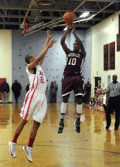 Watervliet's Tyler McLeod takes a jump shot defended by Albany Academy's Ray Jerome during their boy
