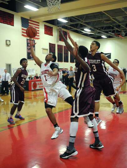 Albany Academy's Darrien White splits Watervliet defenders as he goes in for a basket during their b