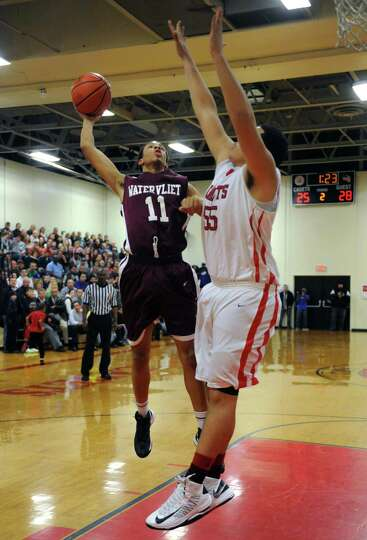 Watervliet's Shane Ray drives to the basket defended by Albany Academy's Marcus Jackson during their