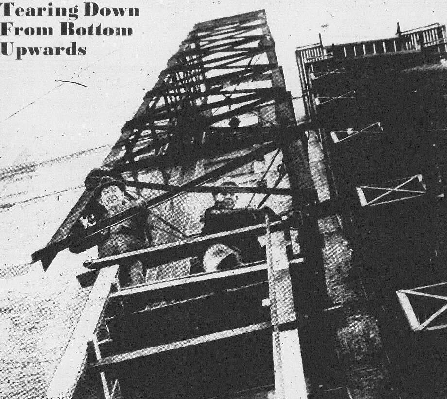 Early Noyyel (left) and T.M. Lamb are at work on the elevator shaft of the Central building which is being torn down. Because falling steel might strike pedestrians below, the shaft is not being dismantled from the top, but removed section by section from the bottom, with the shaft being held against the wall with cables, and lowered down into a wooden scaffold as work progresses. They are working their way up to tearing down, so to speak. Published in the San Antonio Light Feb. 1, 1938. Photo: File Photo