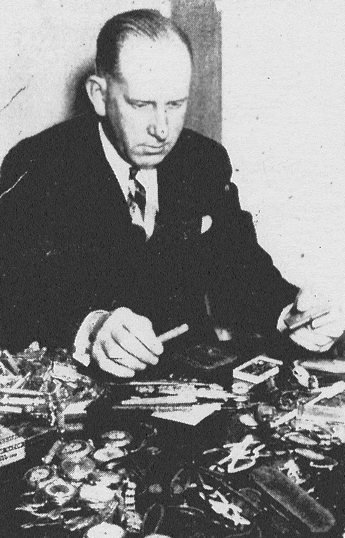 Ed Pytel, Chief of Police Owen Kilday's secretary, with some of the articles to be auctioned Friday by police. Among the articles, loot recovered or lost downtown and turned into police, are watches, safety razors, knives, combs and even a few toothbrushes. Published in the San Antonio Light Feb. 1, 1938.
