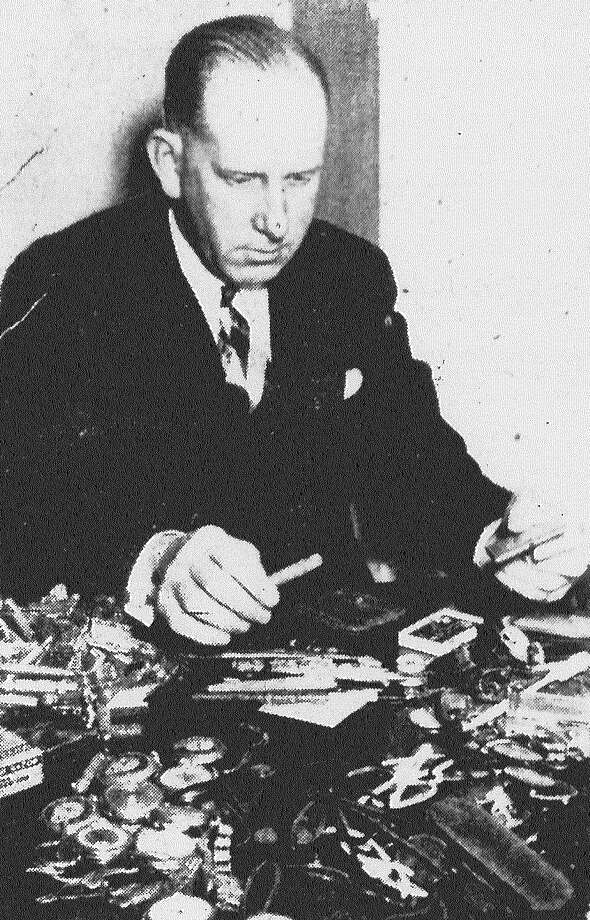 Ed Pytel, Chief of Police Owen Kilday's secretary, with some of the articles to be auctioned Friday by police. Among the articles, loot recovered or lost downtown and turned into police, are watches, safety razors, knives, combs and even a few toothbrushes. Published in the San Antonio Light Feb. 1, 1938. Photo: File Photo