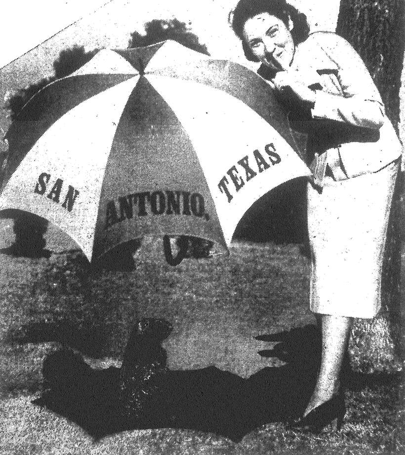 Miss Gladyse Johnson of the Chamber of Commerce takes no chances, holding an umbrella over groundhog so he can't see his shadow, thus assuring balmy weather. Published in the San Antonio Light Feb. 2, 1938. Photo: File Photo