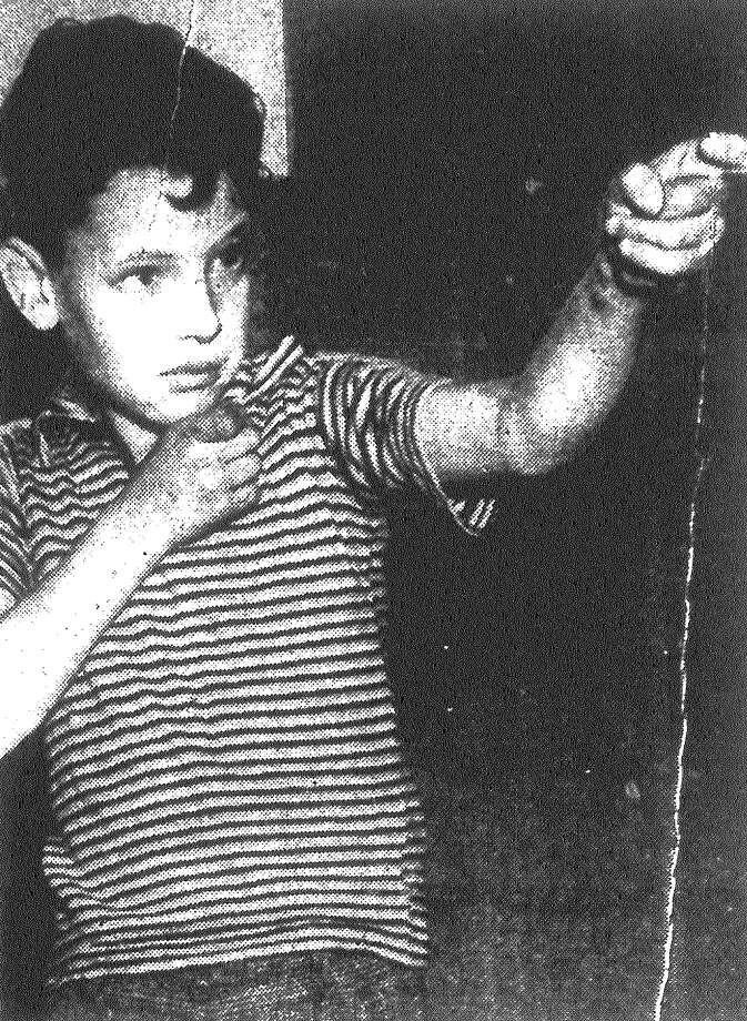 "Harold Guinn, the 8-year-old son of Pvt. Thornton F. Guinn, re-enacts the wounding of Pvt. Jon Saras, 30. Pvt. Guinn, 40, whom Bexar County Sheriff's Deputies describe as a ""jealous husband,"" is accused of striking Pvt. Saras with a shotgun charge, fired at close range, in his left side. The shooting took place at a cafe operated by Mrs. Guinn at 120 Quintana Road, near Camp Normoyle, where both privates are stationed. Published in the San Antonio Light Feb. 1, 1938. Photo: File Photo"