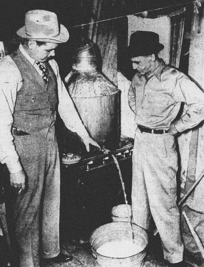 George W. Cox (left) and C.W. Berry, agents of the state liquor control board, seize a 35-gallon still in the kitchen of a home in the 400 block of South Hamilton Street, 30 blocks from town. The agents found 150 gallons of mash and two gallons of whiskey, and arrested Gregorio Alcasio, 32, in connection with the seizure. Agents said Alcasio ran the still because he could find no other work. Published in the San Antonio Light Feb. 5, 1938. Photo: File Photo
