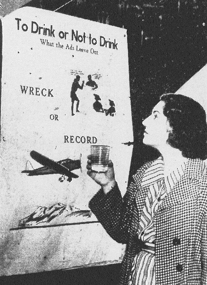 Mary Ruth Jordan examines a dry poster put up by the newly organized Youths' Temperance Council. The association will carry its campaign against alcohol into the barroom, seeking to drive against youthful barflies. Published in the San Antonio Light Feb. 9, 1938. Photo: File Photo