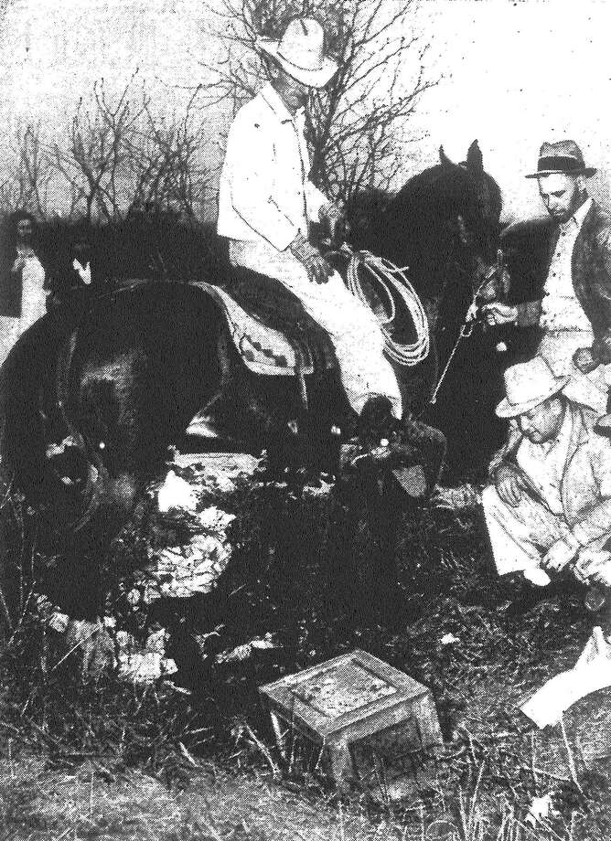 Farmer John Laidley (on the horse), E.Q. Swing (left) and George Ramschissel scrutinize a 250-pound safe taken from Roegelein Provision Company by the slayers of night watchman Max R. Sucrow. The strong box was found abandoned on S.W. 19th Street. The killers, believed to number three or more, pried the safe from its concrete foundation, loaded it onto one of the company's trucks and drove away. The killers then dragged the safe into a ditch, where they failed to open it and hurriedly covered it with brush and departed. According to E.K. Melton, plant manager, the safe contained Monday's receipts, which did not exceed $75 or $80. In addition, the killers took between $3 and $4 from a cash drawer. Published in the San Antonio Light Feb. 8, 1938. Photo: File Photo