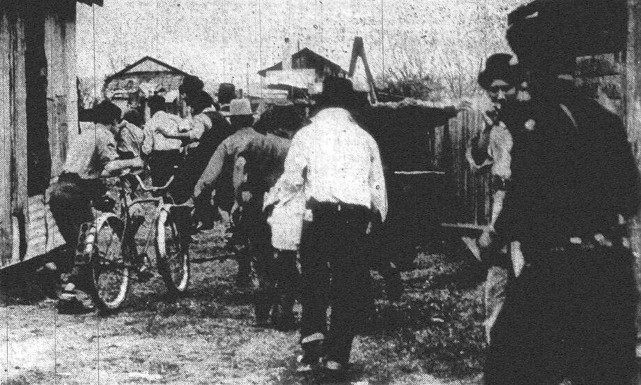 The highlight of the day's activities on San Antonio's pecan shellers' strike front was the arrest of scores of the strikers and the recurrent raids by policemen. Above is shown a policeman (right) hotfooting it after a group of loiterers. Published in the San Antonio Express Feb. 12, 1938. Photo: File Photo