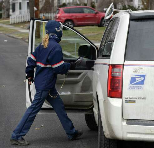 A U. S. Mail letter carrier returns to her car in Albany, N.Y. (Skip Dickstein/Times Union) Photo: SKIP DICKSTEIN
