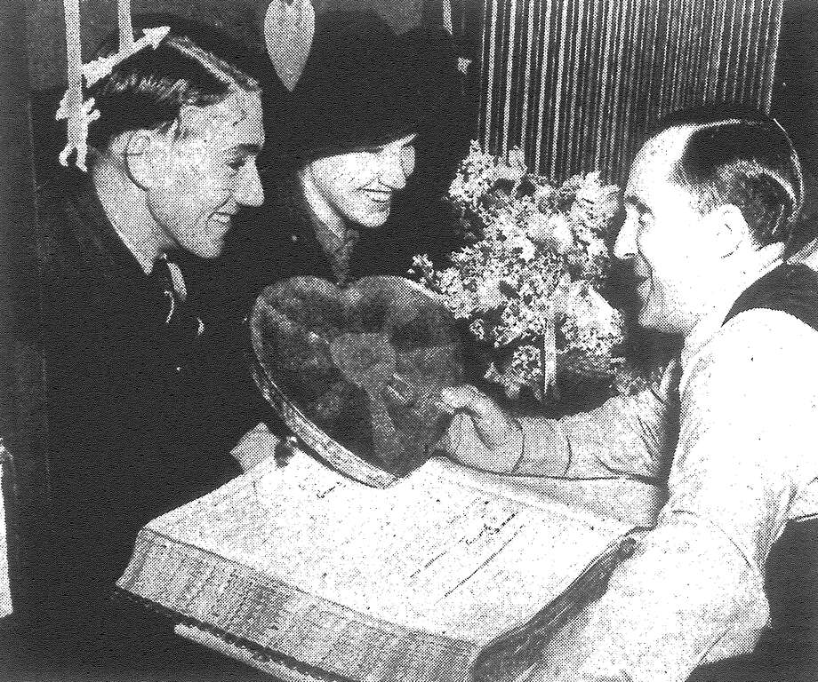 S.H. Wernette, marriage license clerk, got sentimental Monday, decorating his cage and presenting a box of heart candy to Roy A. Hardin of Temple and Mary Louise Casey of Hot Wells, the first couple obtaining a license on Valentine's Day. Others got a sack of candy from the clerk's office. Published in the San Antonio Light Feb. 14, 1938. Photo: File Photo
