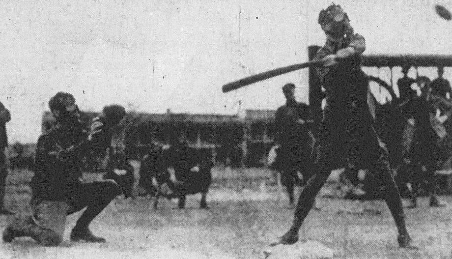 Cpl. M.D. Hallmark of H Company is at bat, with Sgt. J.M. Worth of F Company behind the plate as members of the Second Battalion of the 23rd Infantry play softball at Fort Sam Houston. The troops were wearing gas masks during the game to get accustomed to wearing the masks while undergoing strong exertion. Published in the San Antonio News Feb. 18, 1938. Photo: File Photo