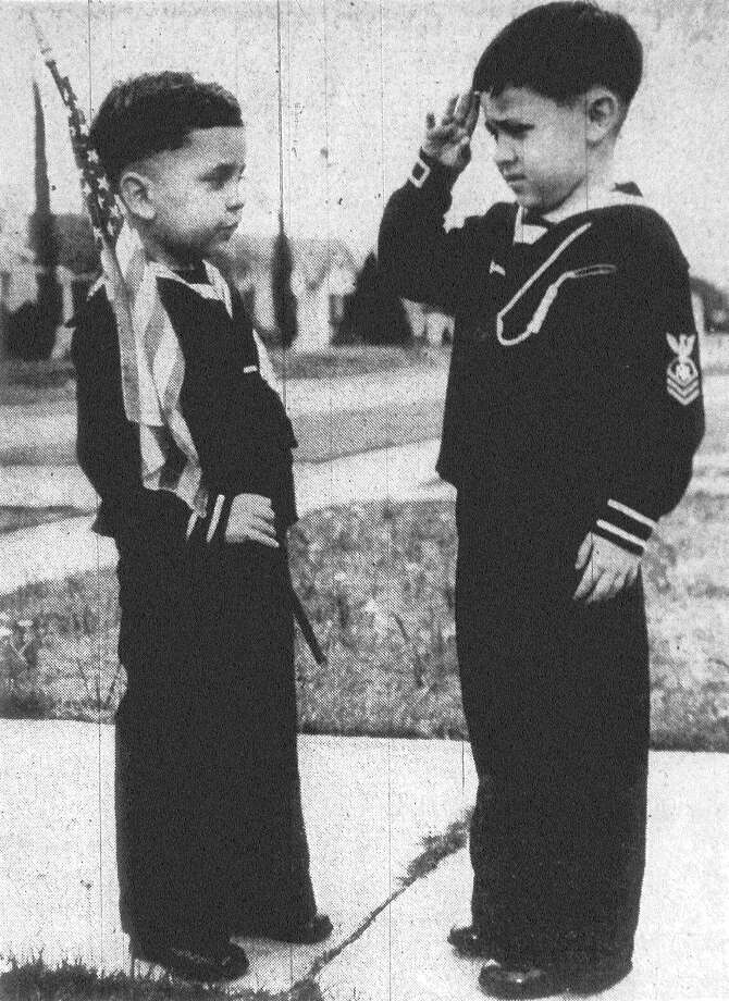 The United States flag, held by Charles Travassos, 4, and saluted by his brother, John, 5, was presented to them by pupils of the Woodlawn Kindergarten where the two boys were students while their father, Capt. Clovis M. Travassos of the Brazilian army learned to fly at Randolph and Kelly fields. Capt. Travassos graduated Wednesday, and will leave with Mrs. Travassos and their sons Saturday for a visit to Mexico City before they return to San Antonio en route to New York City, where they will embark for Rio de Janeiro. Published in the San Antonio Express Feb. 19, 1938. Photo: File Photo