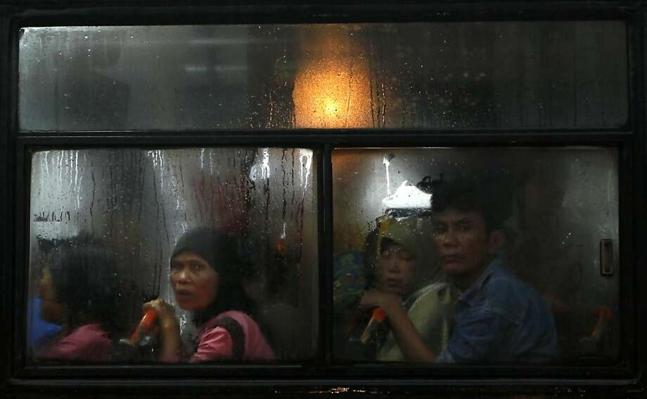 Passengers sit inside a bus stuck in a traffic jam following heavy rain at the main business district in Jakarta, Indonesia, Wednesday, Feb. 6, 2013. About an hour of torrential rain triggered knee-high floods on the main streets of the capital, causing heavy traffic jams. (AP Photo/Dita Alangkara) Photo: Dita Alangkara, Associated Press