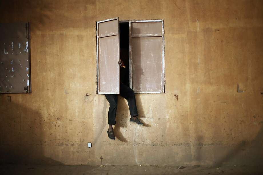 A Malian man sits on a window sill to watch the Nigeria versus Mali Africa Cup of Nations semifinal soccer match taking place in South Africa, in Gao, northern Mali, Wednesday, Feb. 6, 2013. (AP Photo/Jerome Delay) Photo: Jerome Delay, Associated Press