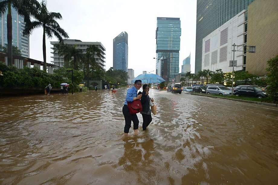 TOPSHOTS  Indonesian people wade through a flooded main street in Jakarta on February 6, 2013. Heavy downpour caused floods on the streets even though Indonesian authorities used generators and cloud-seeding measures to defuse and push away rain-laden clouds. The rainy season is expected to last until March. AFP PHOTO / ADEK BERRYADEK BERRY/AFP/Getty Images Photo: Adek Berry, AFP/Getty Images