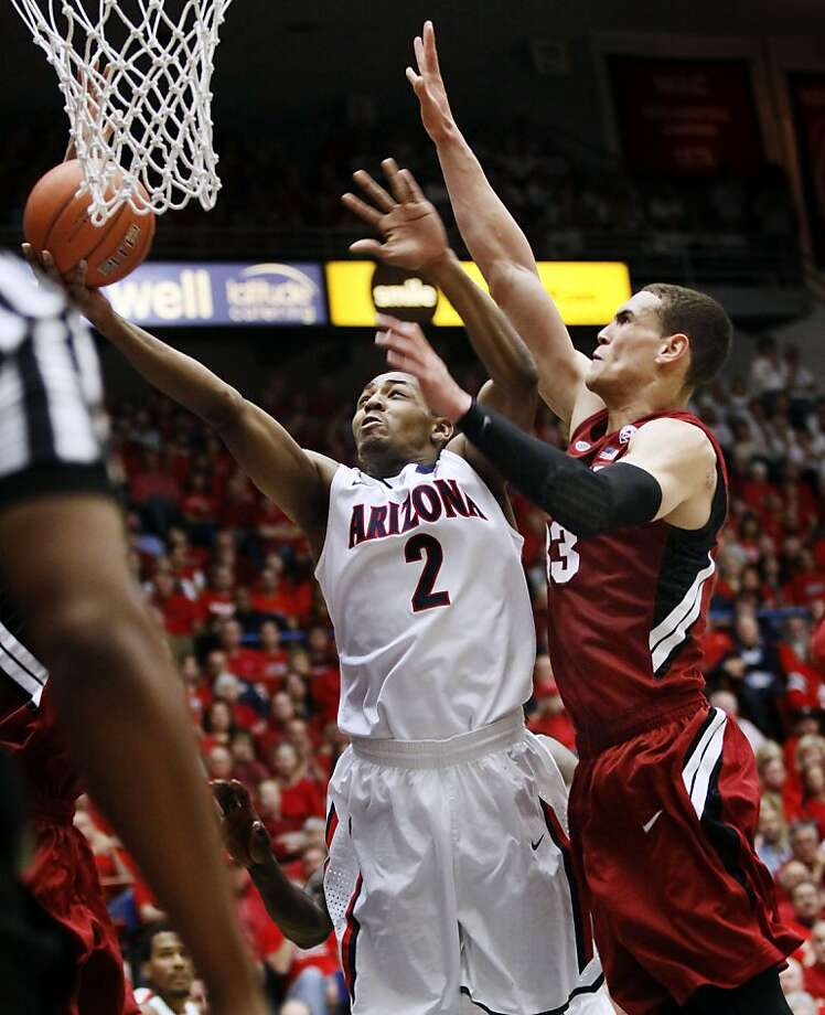 Arizona's Mark Lyons (left), who had 25 points, gets past Stanford's Dwight Powell in the Wildcats' win. Photo: Wily Low, Associated Press