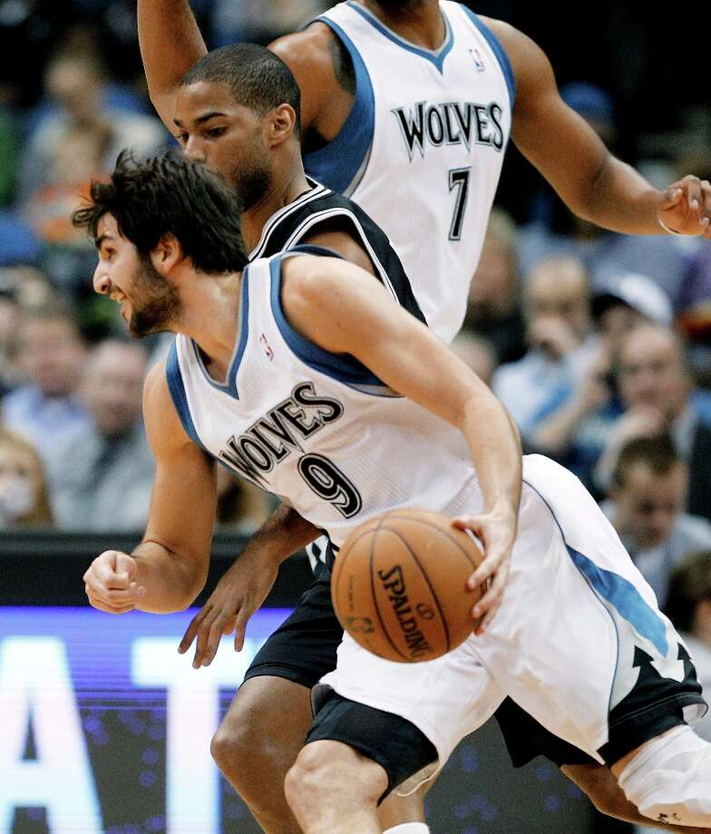Minnesota Timberwolves guard Ricky Rubio (9), of Spain, drives around San Antonio Spurs guard Gary Neal during the first half of an NBA basketball game Wednesday, Feb. 6, 2013, in Minneapolis. Photo: Genevieve Ross, Associated Press / FR170496 AP
