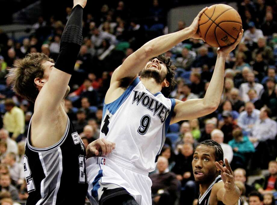 Minnesota Timberwolves guard Ricky Rubio (9), of Spain, drives between San Antonio Spurs center Tiago Splitter, left, of Brazil, and forward Kawhi Leonard, right, during the second half of an NBA basketball game Wednesday, Feb. 6, 2013 in Minneapolis. The Spurs won 104-94. Photo: Genevieve Ross, Associated Press / FR170496 AP