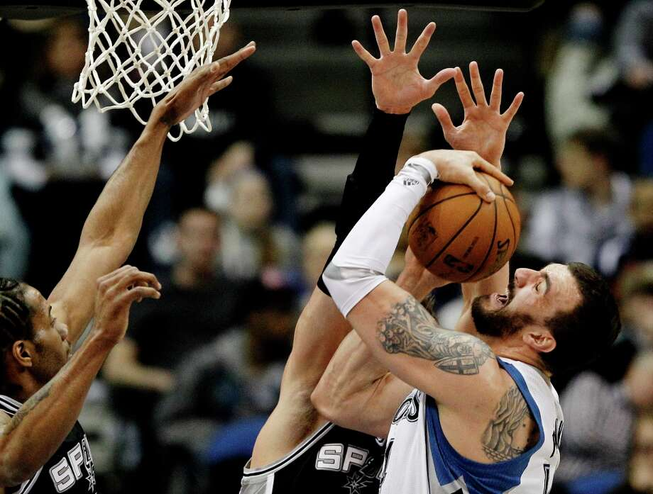 Minnesota Timberwolves center Nikola Pekovic, right, of Montenegro, drives to the basket as San Antonio Spurs forward Kawhi Leonard, left, and center Tiago Splitter defend during the first half of an NBA basketball game Wednesday, Feb. 6, 2013 in Minneapolis. Photo: Genevieve Ross, Associated Press / FR170496 AP