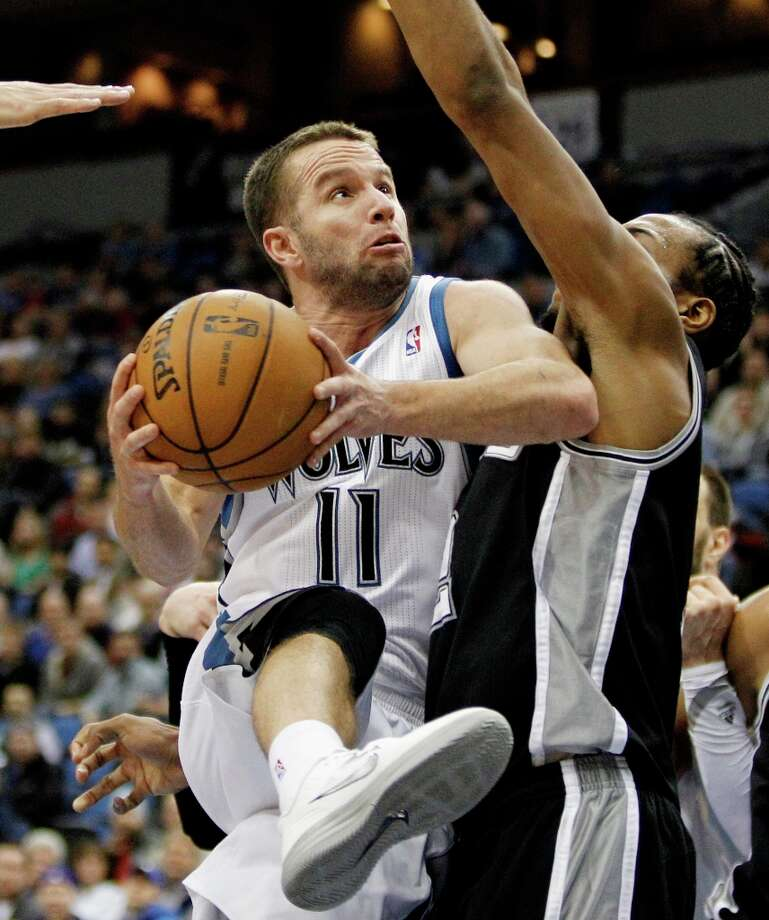Minnesota Timberwolves guard J.J. Barea (11), of Puerto Rico, is stopped short of the basket by San Antonio Spurs forward Kawhi Leonard during the second half of an NBA basketball game Wednesday, Feb. 6, 2013 in Minneapolis. The Spurs won 104-94. Photo: Genevieve Ross, Associated Press / FR170496 AP