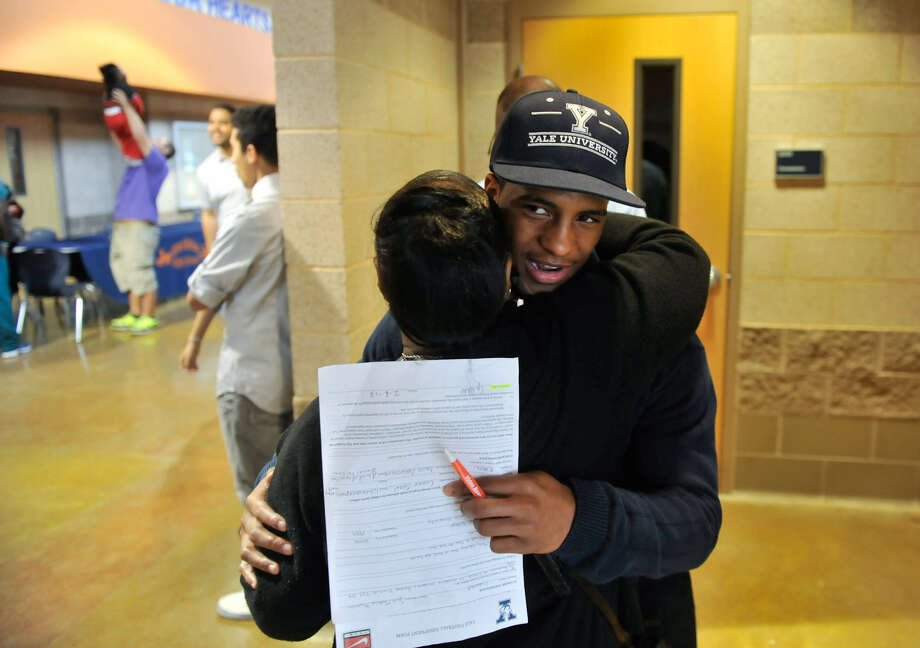 Madison running back Galen McAllister receives a hug from Virginia Hunter congratulating him for signing to play at Yale. Photo: Robin Jerstad / For The Express-News