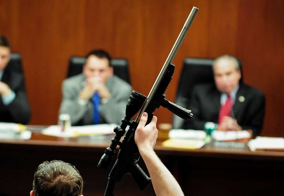 Rob Doar, with the Gun Owners Civil Rights Alliance, holds up a rifle as a visual aid at a hearing on proposed new gun laws with the House public safety committee in the State Office Building in St. Paul, Minn. on Wednesday, Feb.  6, 2013.  Hundreds of people from both sides of the debate swarmed the Capitol office building for the hearing, jamming the committee room and several overflow areas a day after President Barack Obama visited Minneapolis to tout his federal gun-control proposals.  With Democrats controlling the Legislature, new limits on gun access have their best shot at the Capitol in a number of years. But the debate could expose divides between urban Democrats, who represent areas where new gun limits are popular, and rural Democrats from areas with high gun ownership and less support for serious curtailments on the ability to own weapons.  (AP Photo/The St. Paul Pioneer Press, Ben Garvin)  MINNEAPOLIS STAR TRIBUNE OUT Photo: Ben Garvin, Associated Press