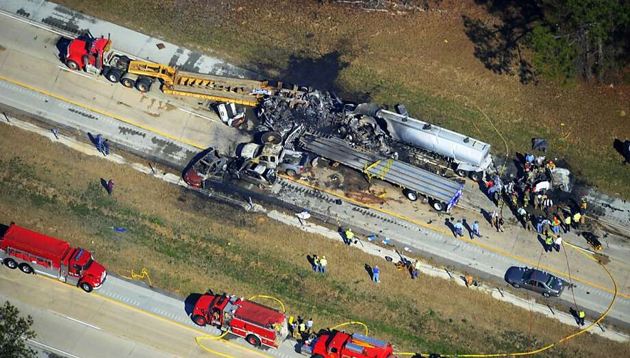 Emergency workers and firemen are at he scene of a pile up on Interstate 16 near Jeffersonville, Ga., Wednesday Feb. 6, 2013.   More than two dozen vehicles collided in a fiery pileup on the foggy Georgia interstate on Wednesday morning, killing at least three people and leaving several others hurt, officials said.  (AP Photo/The Macon Telegraph, Woody Marshall) Photo: Woody Marshall, Associated Press