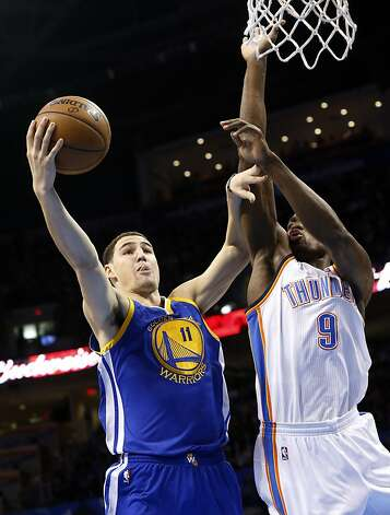 Golden State Warriors guard Klay Thompson (11) shoots in front of Oklahoma City Thunder forward Serge Ibaka (9) during the first quarter of an NBA basketball game in Oklahoma City, Wednesday, Feb. 6, 2013. Oklahoma City won 119-98. (AP Photo/Sue Ogrocki) Photo: Sue Ogrocki, Associated Press