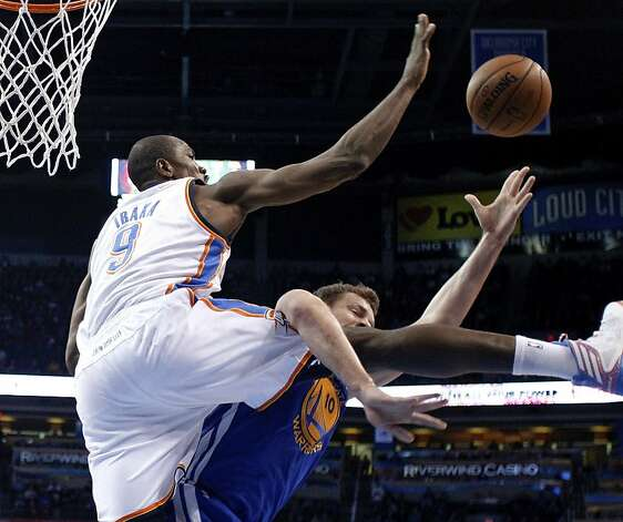 Oklahoma City Thunder forward Serge Ibaka (9) blocks a shot by Golden State Warriors forward David Lee (10) during the first quarter of an NBA basketball game in Oklahoma City, Wednesday, Feb. 6, 2013. Oklahoma City won 119-98. (AP Photo/Sue Ogrocki) Photo: Sue Ogrocki, Associated Press