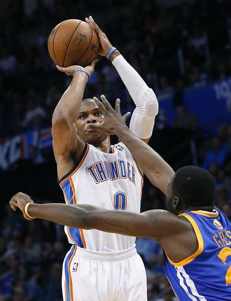 Oklahoma City Thunder guard Russell Westbrook (0) shoots over Golden State Warriors forward Draymond