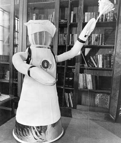 Nov. 6, 1977: Klaatu the Quasar Industries robot appears to perform household chores. The robot wasn't really cleaning -- it was posed in the position and controlled by a hidden operator. Bonus points for including a hat *and* an apron. Other photos showed the robot in a bow tie. Photo: Stan Wolfson/Newsday / ONLINE_YES