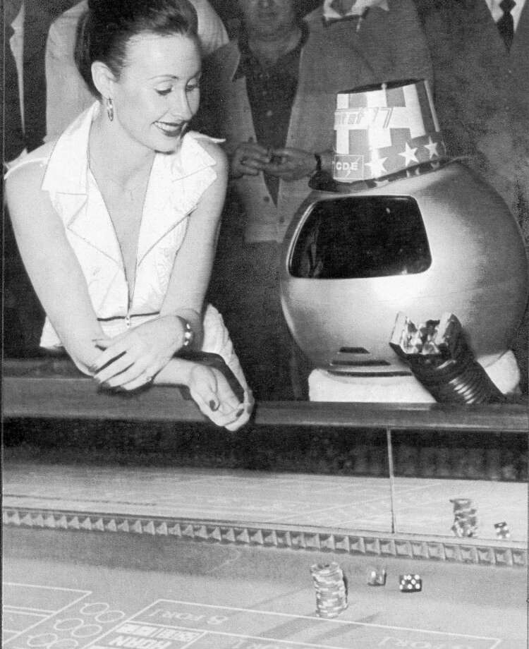 Feb. 26, 1977: A robot plays craps. I don't know why the robot wranglers insisted on putting dumb hats on the robots -- except to improve the illusion that it had human characteristics. Is this woman happy because she's hitting on the robot, or does she have a lot of money on the Don't Pass line? Photo: Chronicle File / ONLINE_YES