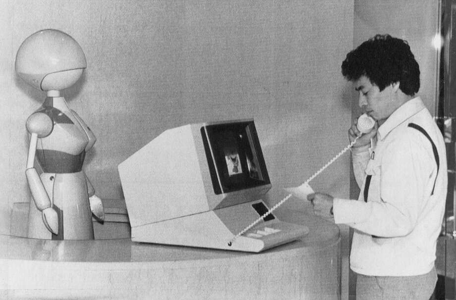 Feb. 11, 1986: A robot receptionist greets a visitor at Namco Limited in Tokyo. She (it?) was programmed to say Welcome to our company in Japanese. It's weird that someone thought to give this robot breasts. That said, I would be 100% behind the Chronicle getting one for our lobby. Photo: Associated Press, The Chronicle / ONLINE_YES