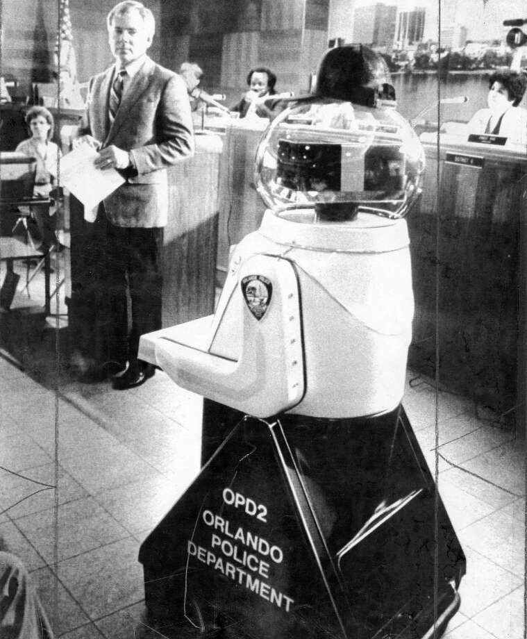 April 25, 1983: Orlando Mayor Bill Frederick looks suspiciously at new crime-fighting robot OPD2. (With trucket cap!) This was a full four years before RoboCop, and thus seemed like less of a bad idea. My guess: OPD2 spent most of his time in a closet, and came out for the Christmas party. Photo: UPI Photo / ONLINE_YES