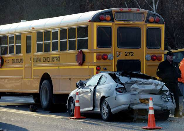 A car sits pinned under the rear of a Guilderland Central School bus this morning Feb. 7, 2013, near the intersection of Route 20 and Helderview in Altamont, N.Y. Injuries were reported at the scene.  (Skip Dickstein/Times Union) Photo: SKIP DICKSTEIN